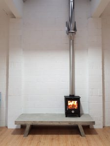Lincsfire Reepham 12kw stove with twin wall flue and concrete hearth in art gallery