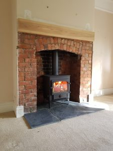 learview Vision with slate hearth in an original brick fireplace with arch