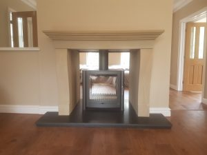 Firebelly FB2 double sided stove installed in a sandstone fireplace