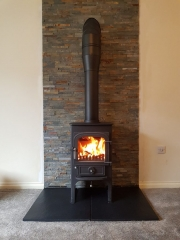 Clearview Pioneer 400P logstore stove with a twinwall flue and split face tiles behind
