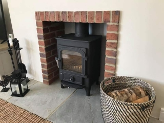 Clearview Pioneer on a sandstone hearth with a brick slip fireplace